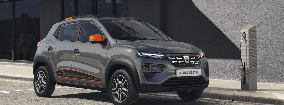 Dacia Spring Electric versión Pack Naranja junto a un punto de recarga