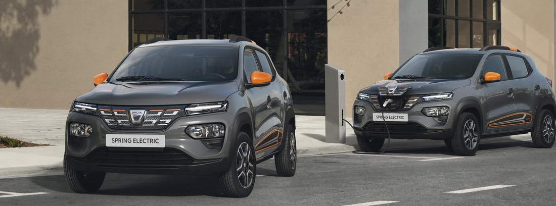 Dos Dacia Spring Electric en versión Pack Naranja junto a un punto de recarga