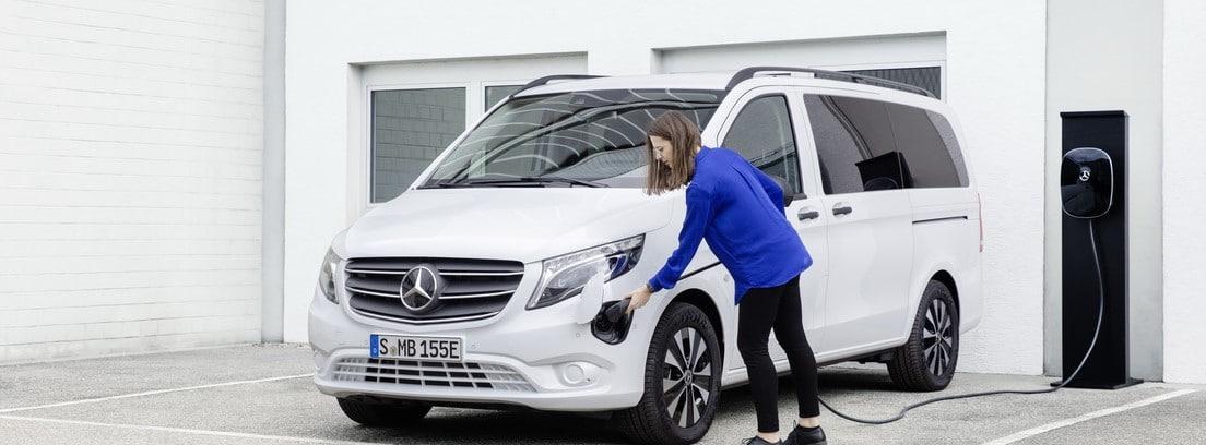 Una chica pone a cargar la nueva furgoneta Mercedes e-VITO Tourer blanca