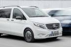 Nueva furgoneta Mercedes e-VITO Tourer blanca circulando por delante de otras furgonetas aparcadas