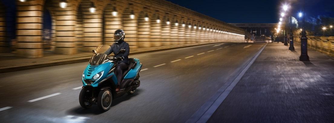 La nueva Peugeot Metropolis 400i en color azul circulando de noche por una ciudad