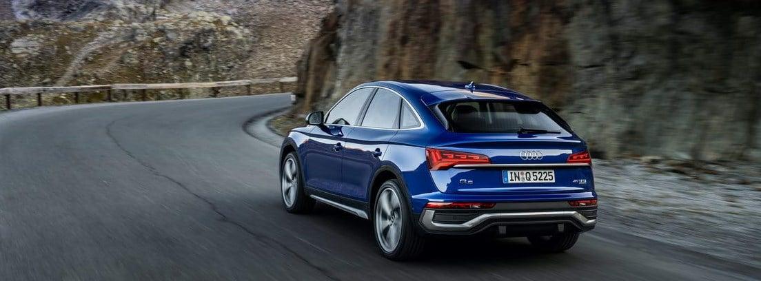 Nuevo Audi Q5 Sportback azul aproximándose a una curva en una carretera entre montañas