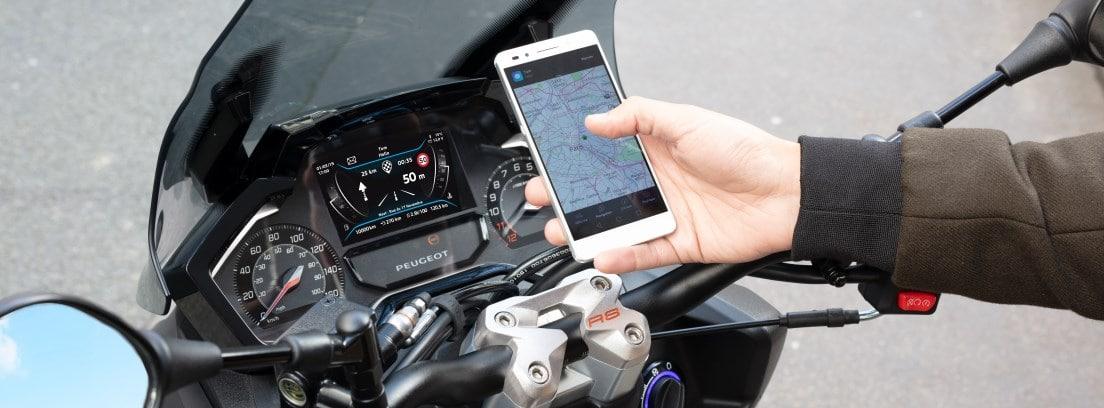 Detalle del cuadro de instrumentos de la Peugeot Pulsion 125 RS con un usuario consultando un smartphone