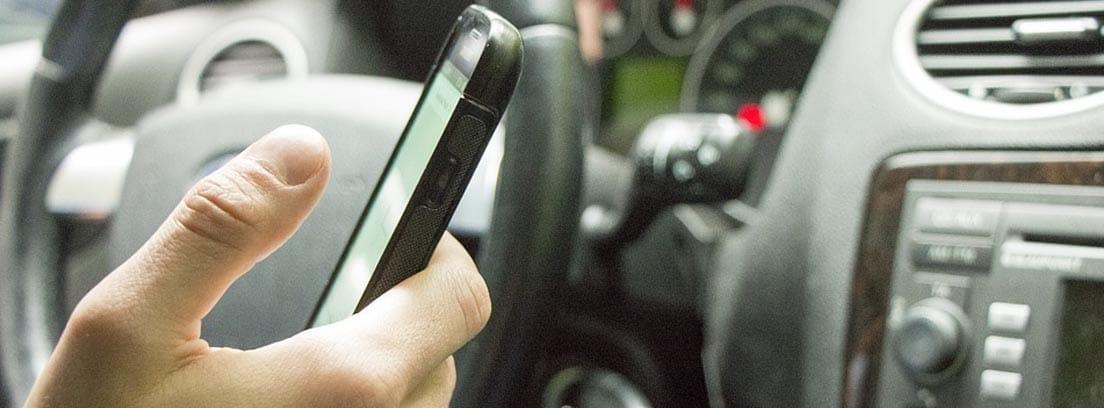 Manos usando un teléfono móvil dentro de un coche