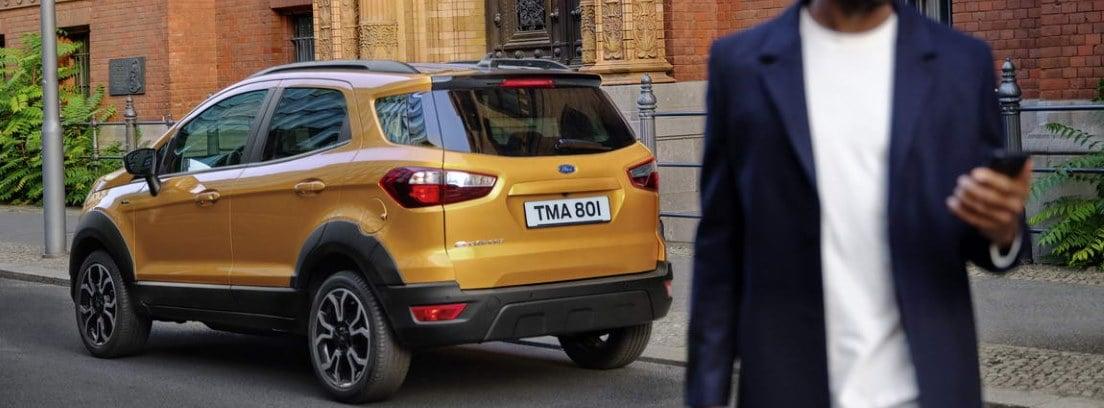 Persona en primer plano mirando un móvil con el nuevo Ford EcoSport Active 2021 detrás aparcado