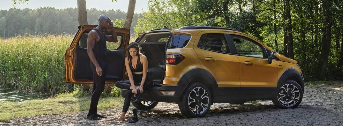 Nuevo Ford EcoSport Active 2021 con la puerta del maletero abierta y una mujer sentada en el maletero y un hombre junto al portón