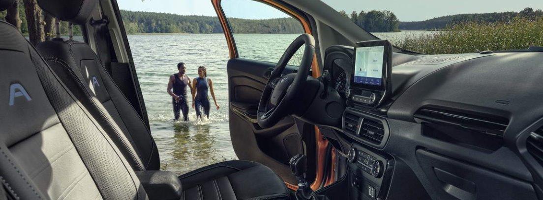 Detalle del habitáculo delantero del nuevo Ford EcoSport Active con la puerta del conductor abierta y con la vista de dos personas en el agua a través de ella