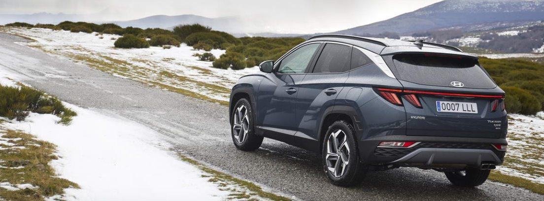 Nuevo Hyundai Tucson 2021 circulando por una carretera rodeada de zonas verde y nieve