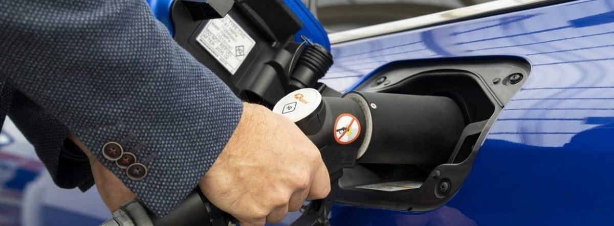 Detalle de las manos de un hombre enchufando para la su carga el nuevo Toyota Mirai 2021 azul