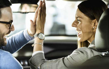 Pareja choca su mano en el interior de un coche