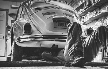 Hombre restaurando un coche Volkswagen Escarabajo clásico