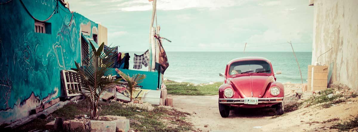 Coche Volkswagen Escarabajo rojo junto al mar