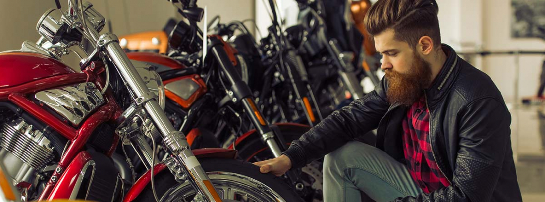 Hombre agachado mirando la rueda de una moto