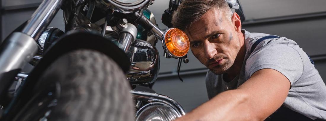 Hombre reparando una moto clásica
