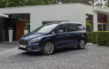 Ford Galaxy Hybrid delante de una casa lujosa