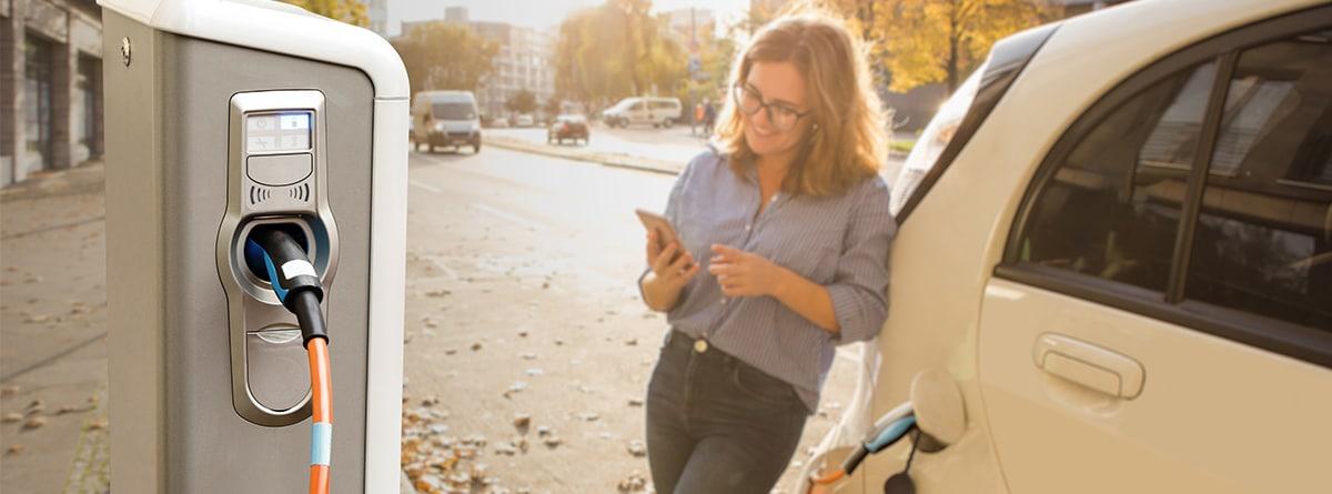 Mujer apoyada en un coche eléctrico conectado a un punto de recarga mirando un móvil