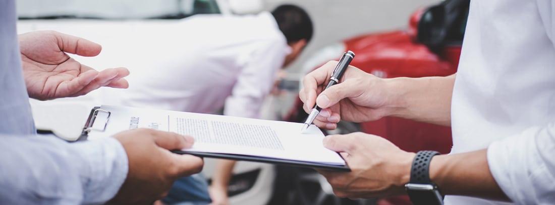 personas firmando un parte de un accidente de coches
