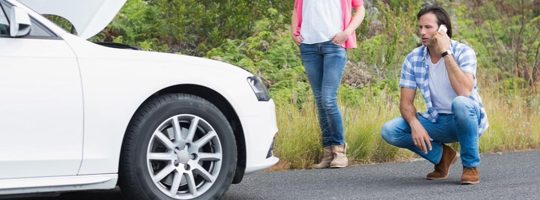 Pareja frente a un coche averiado llamando por teléfono