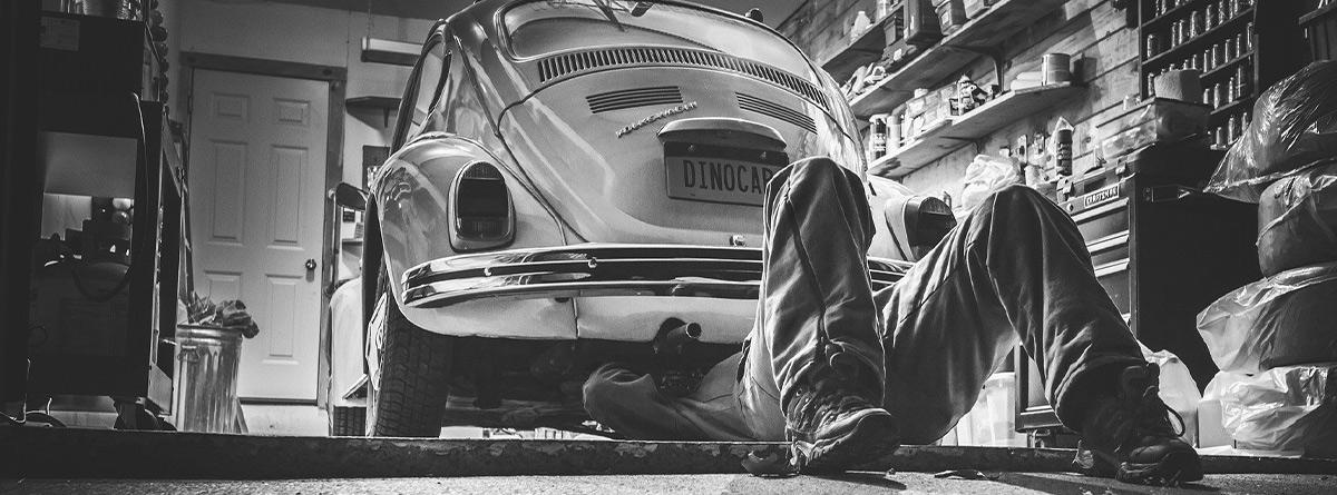 Hombre tumbado en el suelo revisando un coche