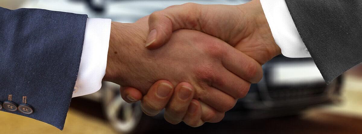 Primer plano de un apretón de manos frente a un coche