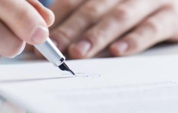 Dos manos firman un documento y de fondo un coche rojo difuminado.