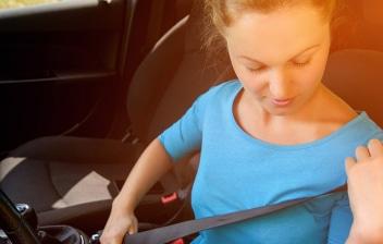 Mujer comprobando un cinturón de seguridad