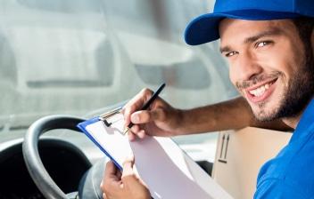 Hombre sonriente tomando notas sobre el volante de un camión