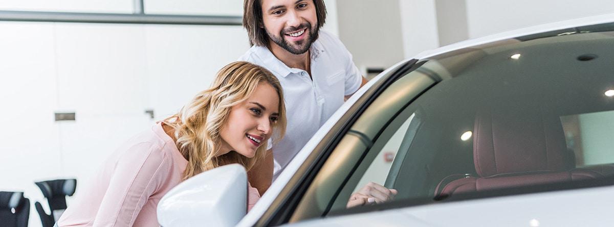 Pareja revisando un coche blanco