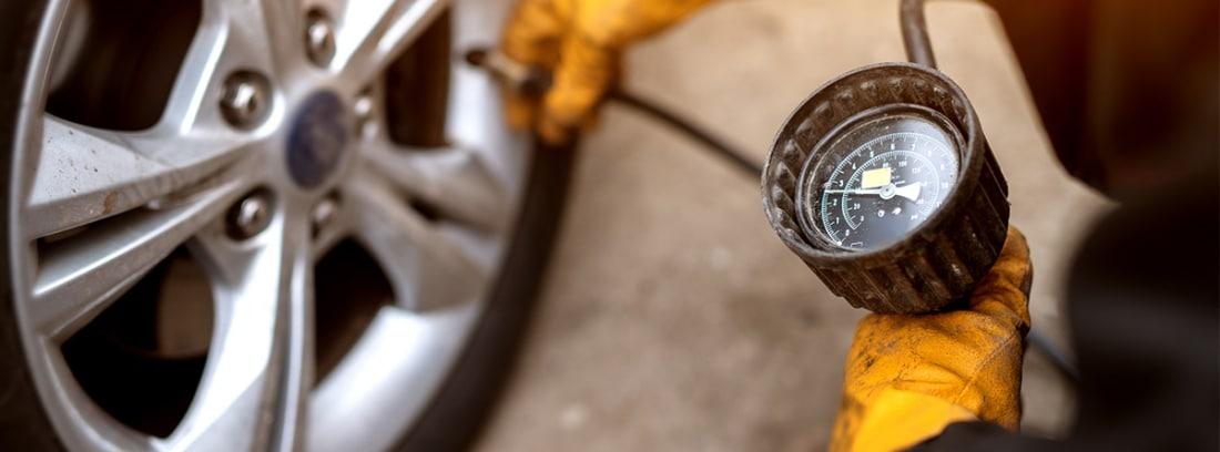 Hombre midiendo la presión de los neumáticos
