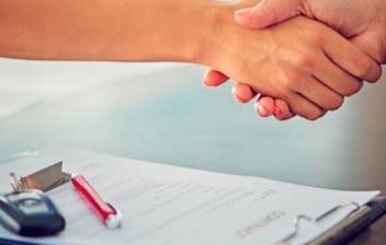 Apretón de manos sobre un contrato con las llaves de un coche