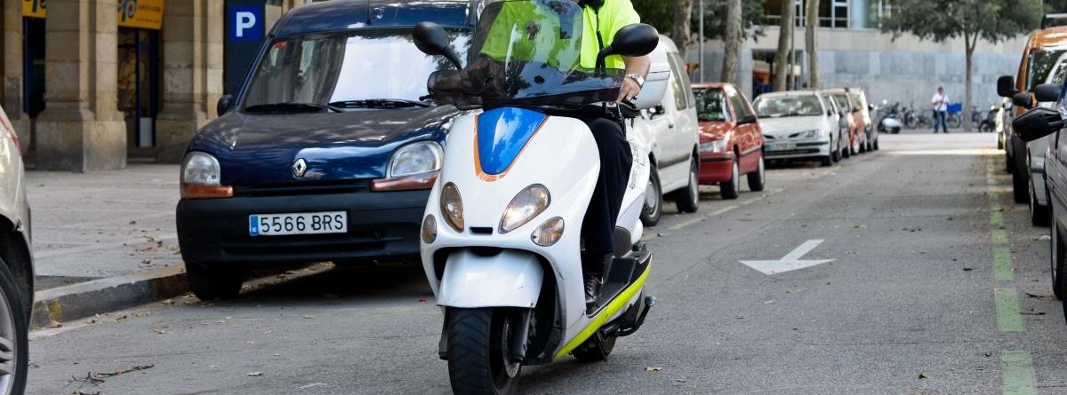 Moto circulando por la calle con coches estacionados a los laterales