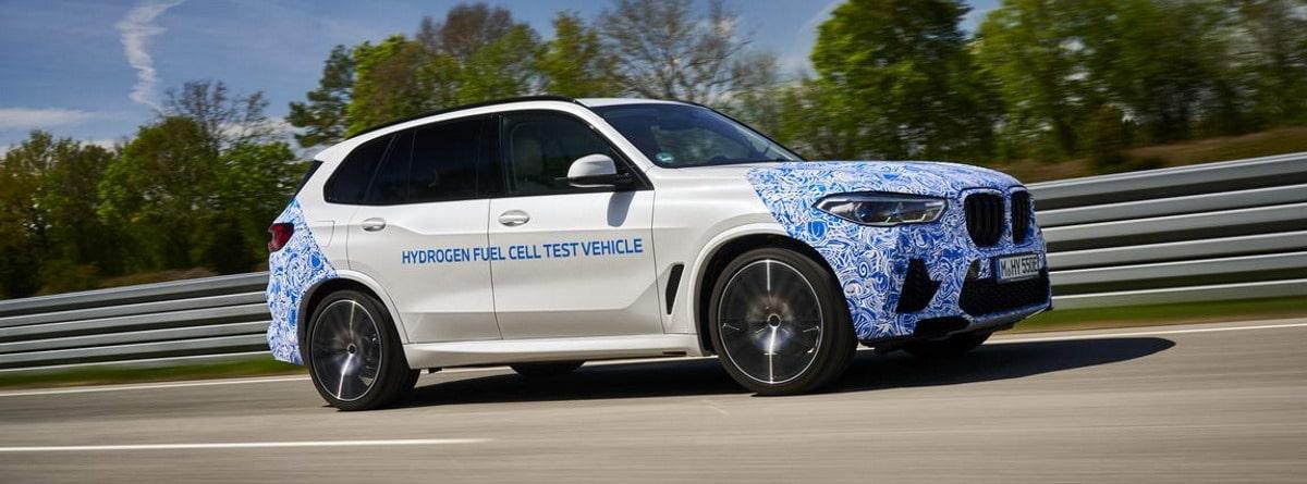 coche BMW i Hydrogen Next circulando por la carretera, se observan sus llantas y diseño exterior blanco y azul