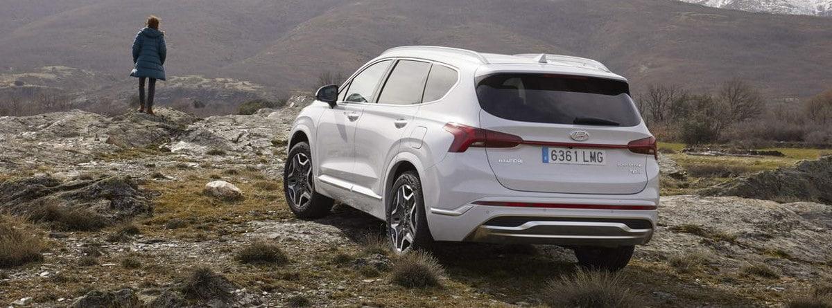 Visión trasera del Hyundai Santa Fe 2021 aparcado en las montañas junto con el conductor