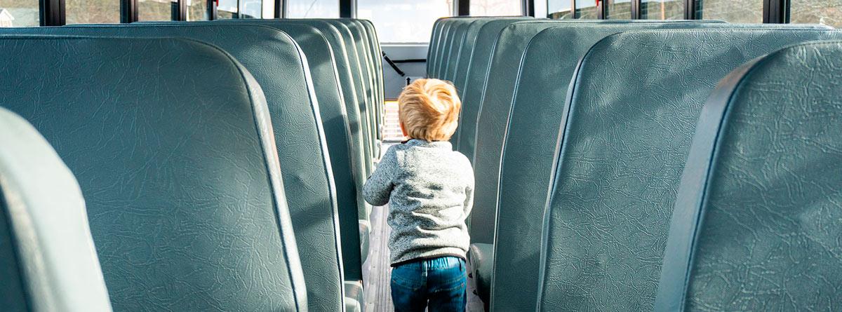 Niño pequeño de espaldas caminando por el pasillo de un autobús