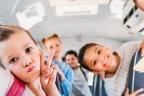 Niños sonrientes dentro de un autobús escolar