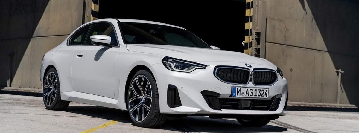 Vista frontal del coche blanco BMW serie 2 Coupé 2021 aparcados en la calle