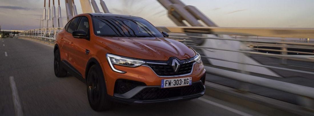 Coche rojo Renault Arkana E-Tech circulando por la ciudad