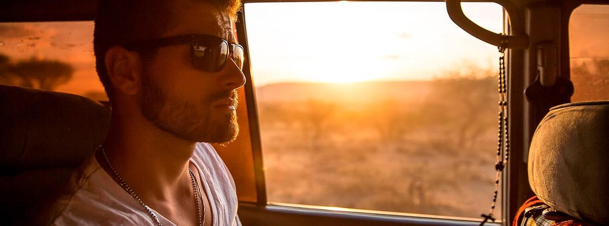 Hombre viajando con gafas de sol en un coche