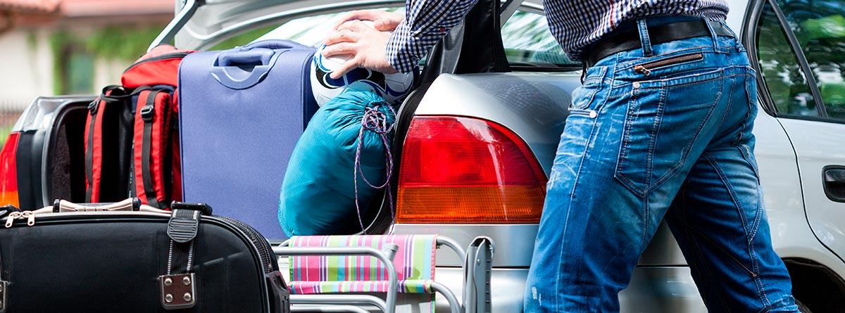 Hombre empujando maletas en un coche muy cargado